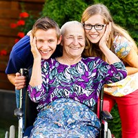 Lady in wheelchair with her carers smiling